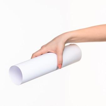 De witte cilinder van de rekwisieten in de vrouwelijke handen op wit met recht schaduw