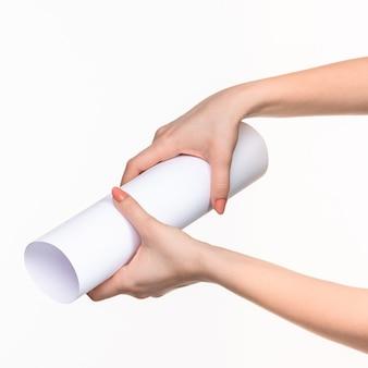 De witte cilinder van de rekwisieten in de vrouwelijke handen op wit