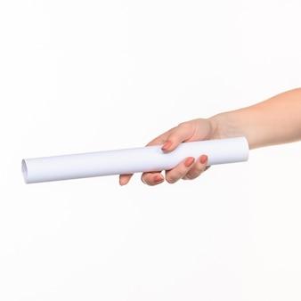 De witte cilinder van de rekwisieten in de vrouwelijke handen op witte achtergrond met rechterschaduw