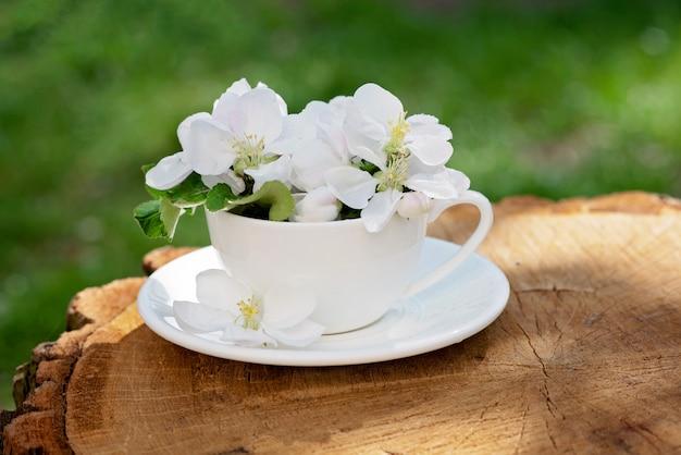 De witte de lenteappel komt bloemen in een koffiekop tot bloei op een natuurlijke houten achtergrond. lente zomer concept. kopieer ruimte.