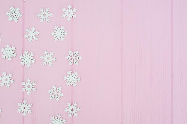 De witte decoratie van kerstmissneeuwvlokken op roze houten