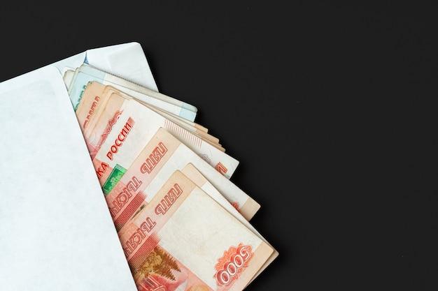 De witte envelop met hoop van russische roebels sluit omhoog