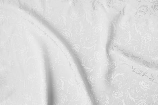 De witte gevouwen achtergrond van de stoffentextuur.