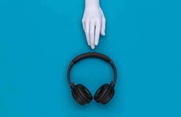 De witte hand van de ledenpop en stereohoofdtelefoons op blauwe achtergrond. bovenaanzicht