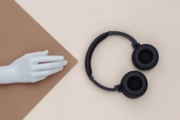 De witte hand van de ledenpop en stereohoofdtelefoons op bruinbeige achtergrond. bovenaanzicht