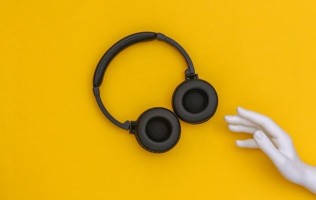 De witte hand van de mannequin raakt een koptelefoon op een gele achtergrond aan. bovenaanzicht
