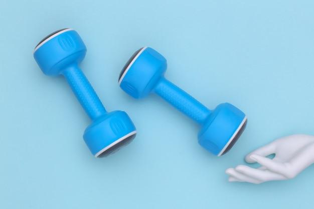 De witte hand van de mannequin raakt plastic halters op een blauwe achtergrond. sport- en fitnessconcept