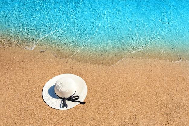 De witte hoed die van het vrouwenstro op tropisch zandstrand leggen met blauw trillend oceaanwater op achtergrond op zonnige de zomerdag. vakanties en bestemming reizen concept.