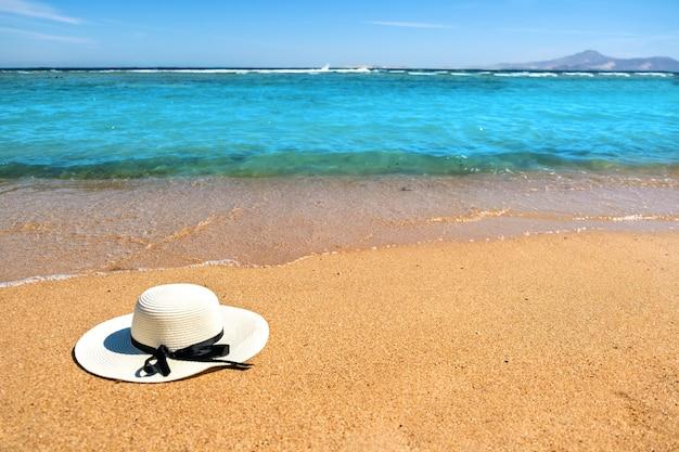 De witte hoed die van het vrouwenstro op tropisch zandstrand leggen met blauw trillend oceaanwater, zonnige de zomerdag. vakanties en bestemming reizen concept.