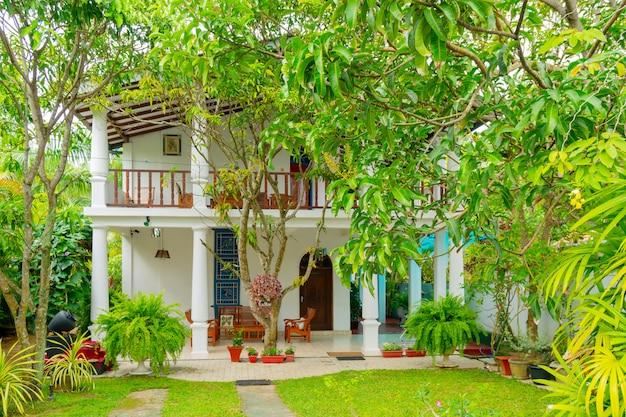 De witte hotelbouw onder groene tropische installaties.