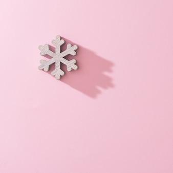 De witte houten decoratie van de sneeuwvlokkerstboom met roze achtergrond. minimale nieuwjaar winter vakantie concept. plat leggen.