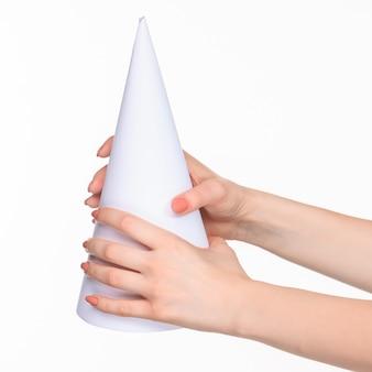 De witte kegel van de rekwisieten in de vrouwelijke handen op wit met de juiste schaduw