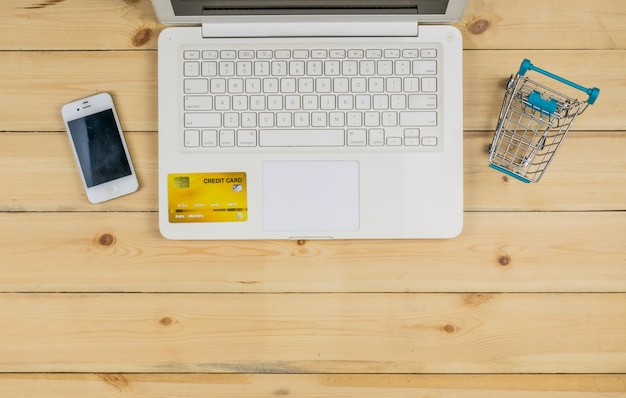 De witte laptop met smartphone, creditcard en het winkelwagentje op de houten tafel. e-commerce winkelen.
