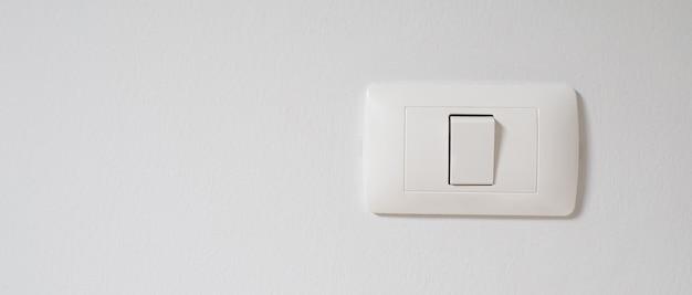De witte lichtschakelaar zit aan de muur.