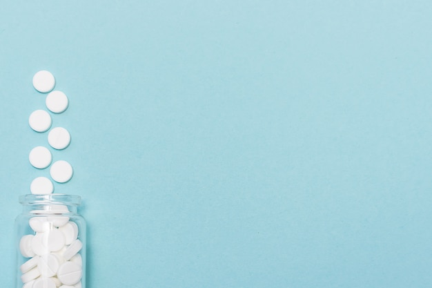 De witte medische tabletten in glasfles op blauw, sluiten omhoog.