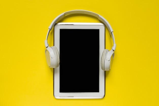 De witte moderne hoofdtelefoons en de tablet op trending gele backgoundvlakte leggen hoogste meningsruimte voor tekst