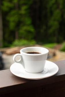 De witte mok donkere hete koffie in de ochtend op houten hek met bos achtergrond.