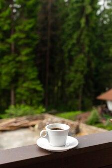 De witte mok donkere warme ochtendkoffie op houten hek met bosachtergrond.