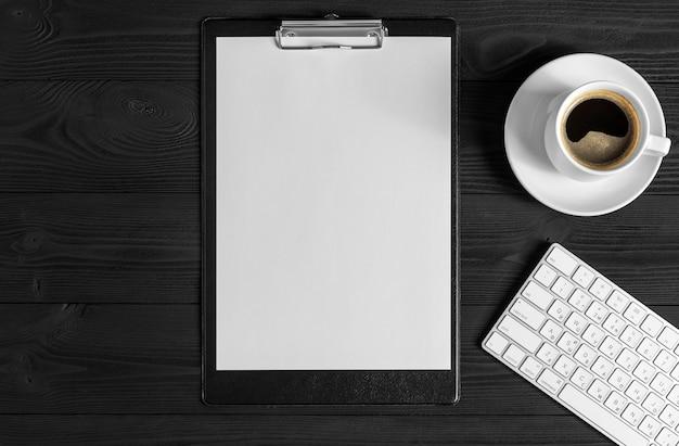 De witte open kladblok en computer toetsenbord, muis, mobiele, koffie geïsoleerd op de houten bureaublad