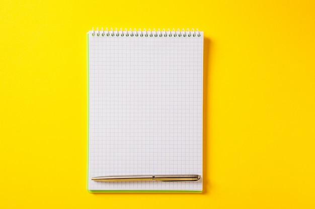 De witte open kladblok op zilveren pen geïsoleerd op geel