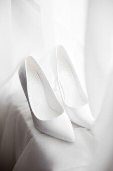 De witte schoenen van de bruid staan op een witte vensterbank