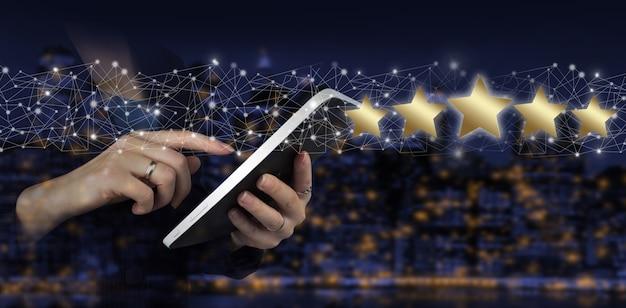De witte tablet van de handaanraking met digitaal hologram vijf sterrenteken op stads donkere onscherpe achtergrond. verhoog beoordeling of rangschikking, evaluatie en classificatieconcept.