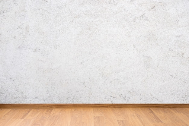 De witte textuur van de cementmuur en bruine houten vloer