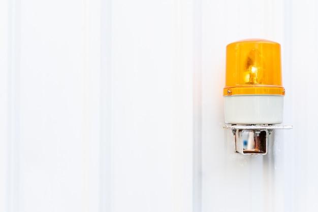 De witte textuur van de golfmetaalmuur met geel noodsituatielicht.