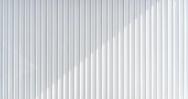 De witte textuur van de golfmetaalmuur met gietende schaduw.