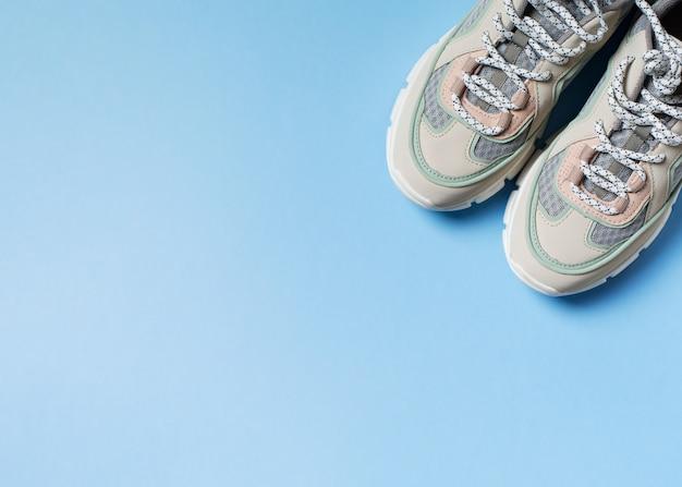 De witte vrouwelijke vlakte van de tennisschoenmanier legt op blauwe achtergrond