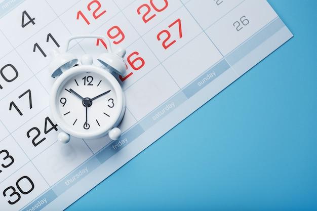 De witte wekker staat op de kalender met data