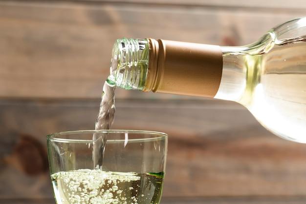 De witte wijn van de close-up die in een glas wordt gegoten