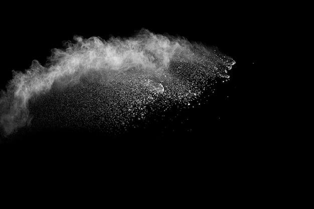 De witte wolk van de poederexplosie tegen zwarte achtergrond. witte stofdeeltjes spetteren