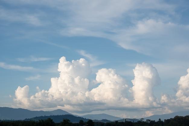 De witte wolken hebben een vreemde vorm en een berg, de lucht en de open ruimte hebben bergen beneden, wolken zweven boven de bergen.