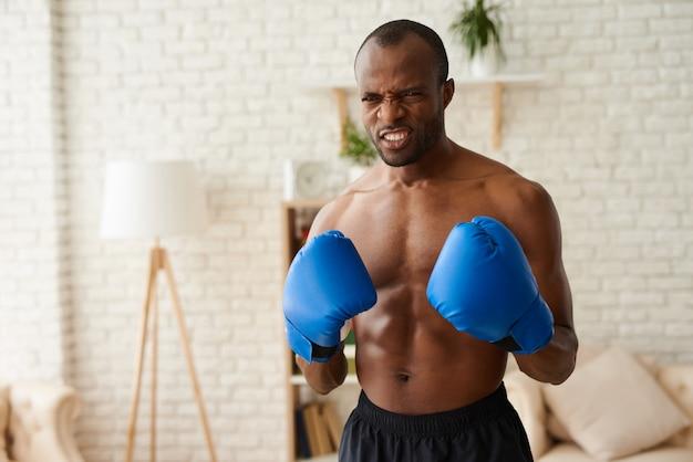 De woedende mens in bokshandschoenen bevindt zich in het vechten houding.