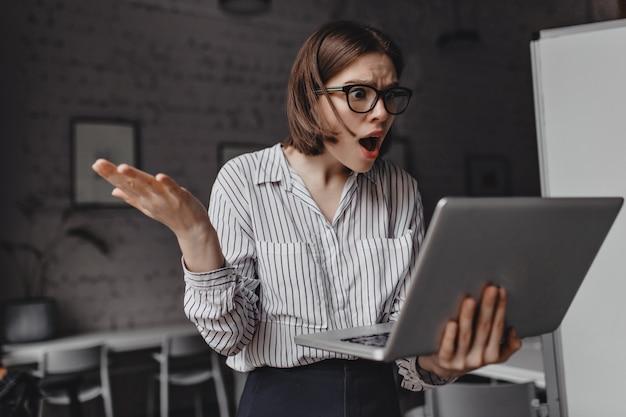 De woeste zakenvrouw kijkt verontwaardigd en geschokt in laptop en spreidt haar armen tegen de achtergrond van de witte werkplek.