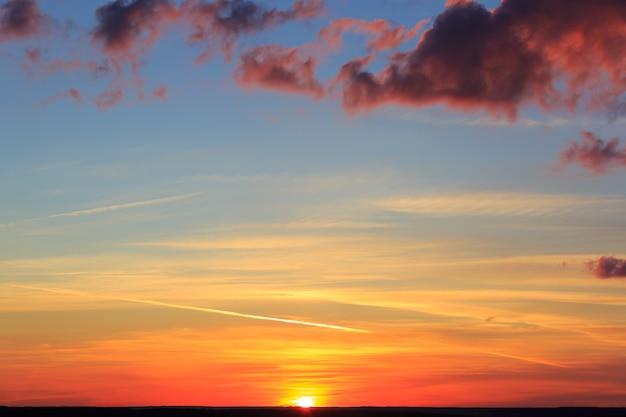 De wolken worden verlicht door het felle rode licht van de ondergaande zon