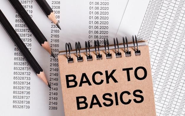 De woorden back to basics staan op het bruine notitieboekje. potloden in de buurt.
