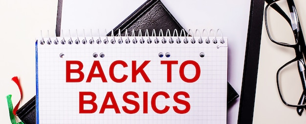 De woorden back to basics zijn in het rood geschreven in een wit notitieboekje naast een bril met een zwart montuur.