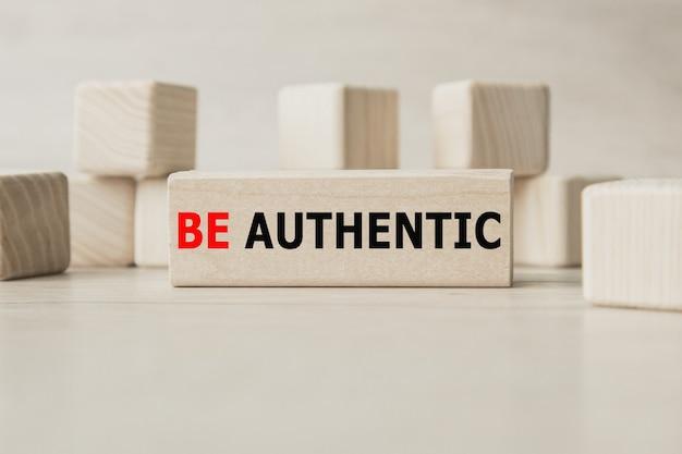 De woorden be authentic zijn geschreven op een houten kubusstructuur.