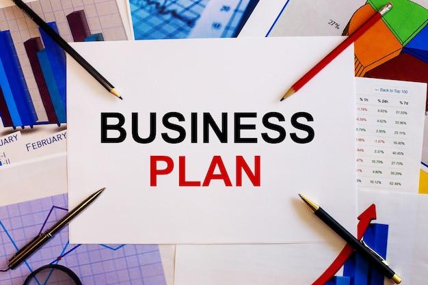 De woorden business plan wordt geschreven op een witte achtergrond in de buurt van gekleurde grafieken, pennen en potloden
