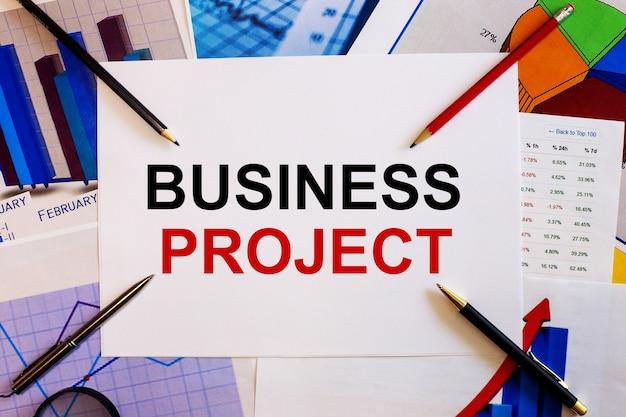 De woorden business project worden geschreven op een witte achtergrond in de buurt van gekleurde grafieken, pennen en potloden