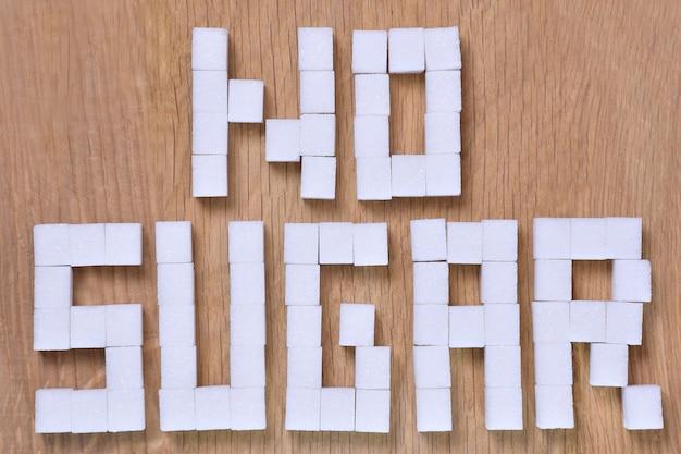 De woorden geen suiker, bekleed met blokjes geraffineerde suiker op een bruine houten ondergrond, zijn verboden. detailopname
