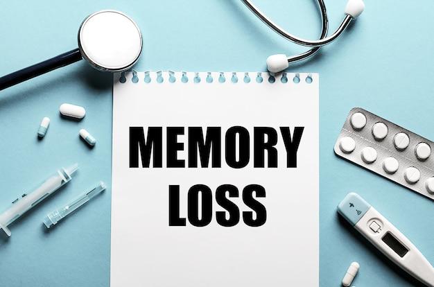 De woorden geheugenverlies geschreven op een witte blocnote op een blauwe achtergrond in de buurt van een stethoscoop, spuit, elektronische thermometer en pillen