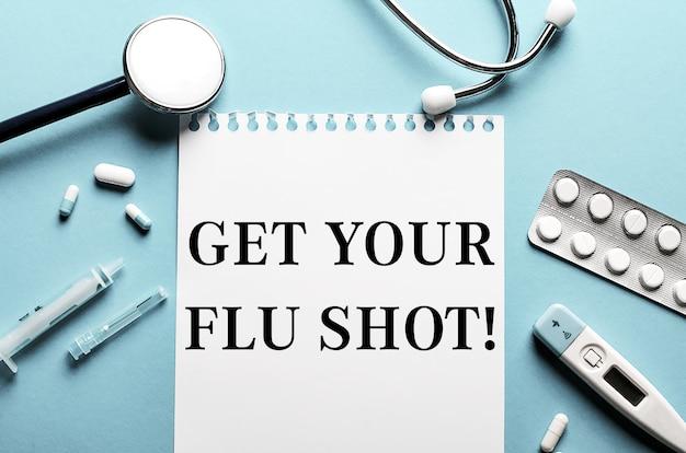 De woorden get you flu shot geschreven op een wit notitieblok op een blauw oppervlak in de buurt van een stethoscoop, spuit, elektronische thermometer en pillen