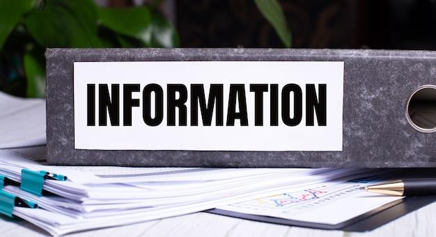 De woorden informatie zijn geschreven in een grijze map naast documenten. bedrijfsconcept