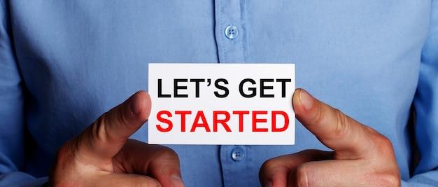De woorden let is get started zijn geschreven op een wit visitekaartje in de handen van een man. bedrijfsconcept