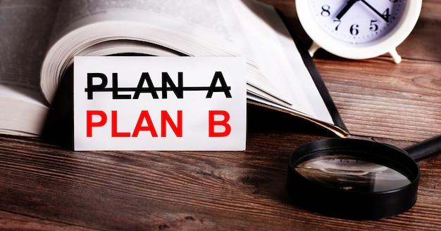 De woorden plan b geschreven op een witte kaart naast een open boek, een wekker en een vergrootglas