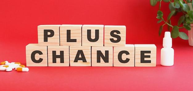 De woorden plus chance is gemaakt van houten kubussen op een rood oppervlak met medicijnen. medisch concept.