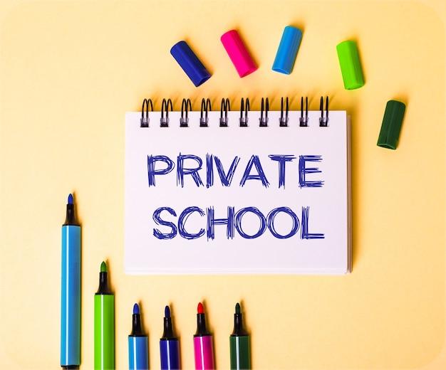 De woorden private school geschreven in een wit notitieboekje op een beige achtergrond in de buurt van veelkleurige markeringen